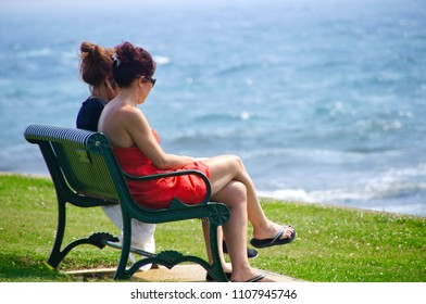Newport, Rhode Island/USA- July 19, 2013: A horizontal image of two young women sitting on a park bench in the green grass overlooking the Atlantic Ocean.