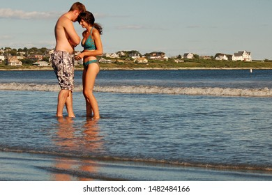 Newport, RI, USA August 17, 2007A young adult couple stand close to each other as they wade in the sea at a beach in Newport, Rhode Island