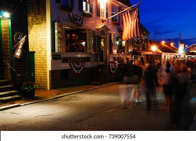 Newport, RI, USA July 3, 2009 A crowd mills around on a summer's night on Bowen's Wharf in Newport, Rhode Island.  The area is known for upscale dinging and shopping.