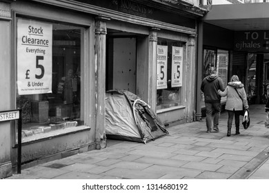 Newport, Wales - Feb 16, 2019: Homeless Tent in Doorway of Close Down Store, black and white street photography, shallow depth of field