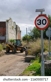 Newport Wales UK 08/20/2012: 30 MPH road sign with industrial JCB machinery and derelict building in background