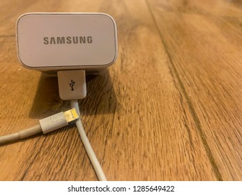 Newport,Gwent,Wales,16/01/2019 An Apple charger cable connected to an Android Samsung charger. Visual representation of Apple versus Android or Apple collaboration with Android.