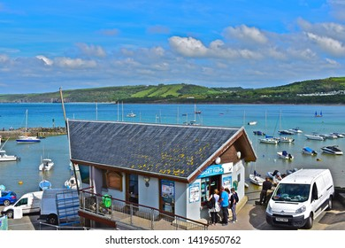Newquay, Ceredigion / Wales UK - 5/30/2019: A view of the pretty harbour of Newquay in West Wales, with people queuing to buy tickets for local boat trips. The distant coastline forms the background.