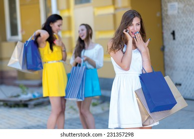 News about shopping sales on mobile phone. Young and pretty girl is talking on the sell phone and holding a shopping bags. Her friends girls are standing on the background with shopping bags.