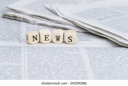 News formed by wooden letters, on top of newspapers