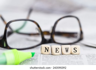 News formed by wooden letters, on top of newspapers with glasses and pen
