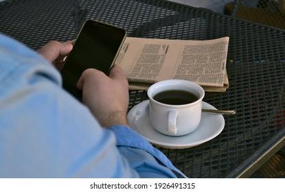 Nachrichten auf einem Smartphone am Tisch mit einer Tasse Kaffee