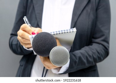 News reporter or TV journalist at press conference or media event, holding microphone and writing notes. Broadcast journalism concept.