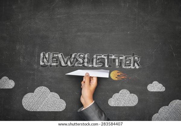 Newsletter concept on black blackboard with businessman hand holding paper plane