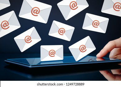 Newsletter and email marketing concept. Hand touching tablet showing email icons on dark background.