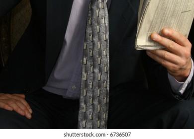 Newspaper being held by man over black wearing suit.