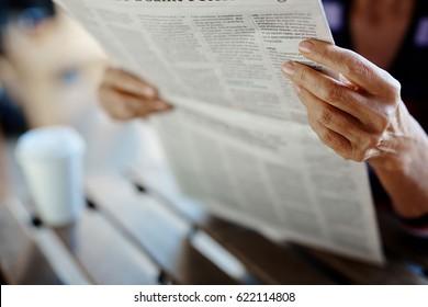 Newspaper broadsheet held and read by senior female