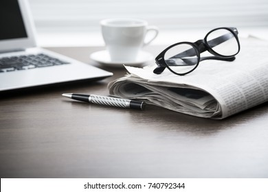 Newspaper with computer on table.