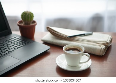 Newspaper with computer on table. Coffee break.