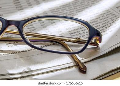 newspaper full of interesting news and reading glasses
