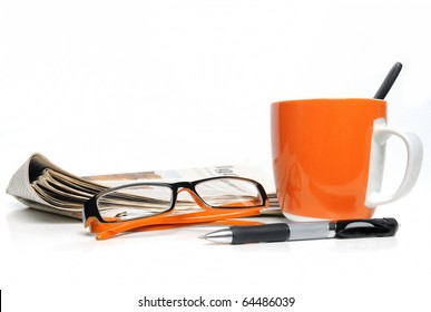 Newspaper, glasses, cup of coffee and ballpoint on white background