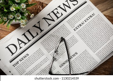 Newspaper with the headline and glasses on wooden table, Daily Newspaper mock-up concept