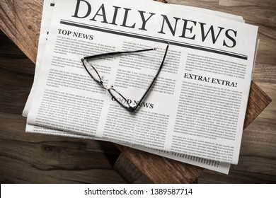 Newspaper with the headline News with glasses on wooden table, Daily Newspaper mock-up concept
