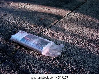 Newspaper on asphalt driveway