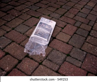Newspaper on brick driveway