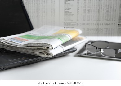 Newspaper on laptop with blurred newspaper background