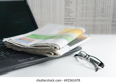 Newspaper on laptop with blurred newspaper background with glasses