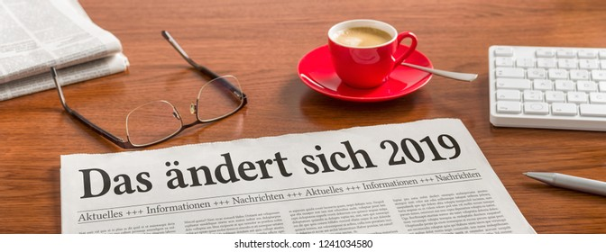A newspaper on a wooden desk with the german headline Das aendert sich 2019 - Changes coming in 2019