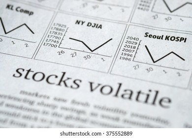 """Newspaper open to stock market page showing word """"Stocks Volatile"""".Concept of studying and trading the stock markets"""