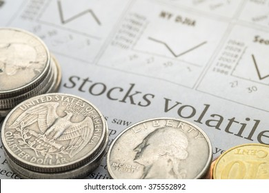 """Newspaper open to stock market page showing word """"Stocks Volatile"""" and coins. Concept of Investment."""