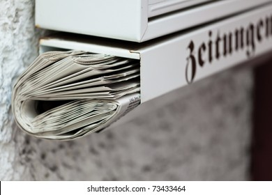 A newspaper was placed in a mailbox. Delivery of daily newspaper