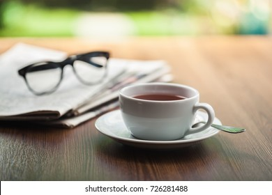 Newspaper reading glasses coffee cup.
