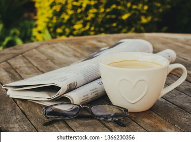 Newspaper, reading glasses and a cup of coffee on a wooden table, outdoors.