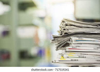 newspaper stack put on the table in library. Newspapers are always available with libraries.But the number of newspapers in the stack is decreasing.As people turn to read more data on the Internet.