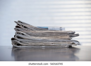 Newspaper stacked. Pile of newspapers on a wooden table. Curtain shadows in the background on a wall.