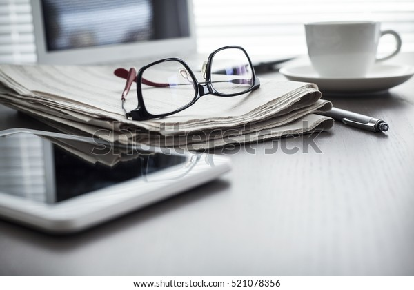 Newspaper with tablet on table