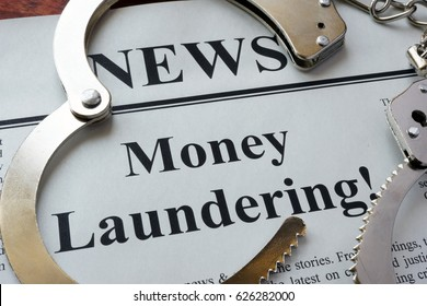 Newspaper with title Money laundering and handcuffs.