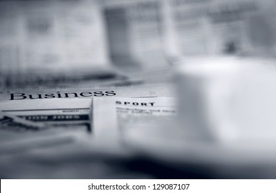 Newspapers and coffee cup macro shot with shallow depth of field
