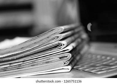 Newspapers and computer. Laptop and daily papers on the table. Fresh news by  paper or by electronic device, different ways of communication. Source of information, actual data on pages or on screen