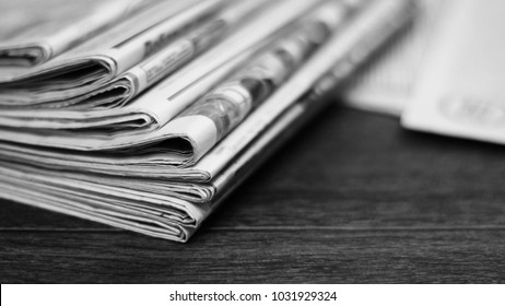 Newspapers and documents. Daily paper with news on wooden table. Pages with text, articles and headlines. Concept for business and information, press and media. Close up, side view