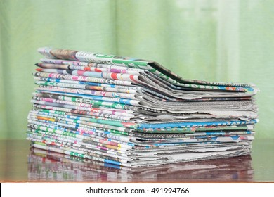 Newspapers folded and stack on wood table.