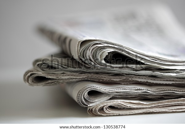 Newspapers folded and stacked concept for global communications