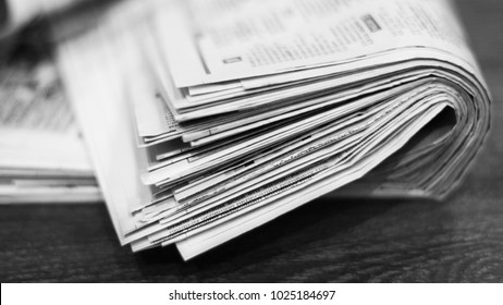 Newspapers. Folded and stacked daily papers with news on wooden table. Fresh morning press with business and finance information in the office. Side view, selective focus