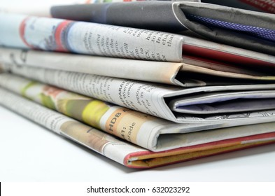 Newspapers folded and stacked isolated on white