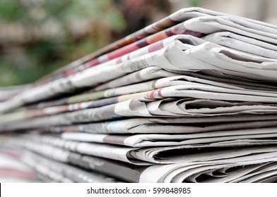 Newspapers folded and stacked on the table with garden. Closeup newspaper and selective focus image. Time to read concept.