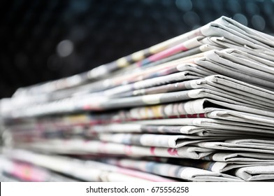 Newspapers folded and stacked on the table modern dark background. Closeup newspaper and selective focus image.