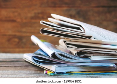 Newspapers and magazines on old wood background. Toned image.