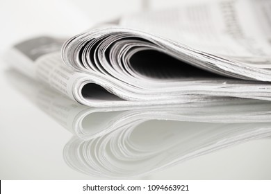 Newspapers mirrored on glass table against plain background with shallow depth of field