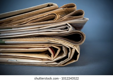 Newspapers on blue background with shallow depth of field