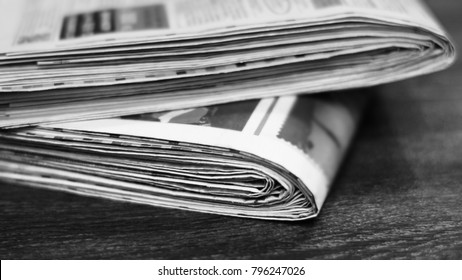 Newspapers on wooden table. Daily papers with fresh news. Folded and stacked pages with headlines, articles and photos. Selective focus on paper edges with blurred text, background texture