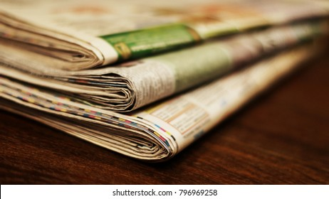Newspapers. Pile of folded and stacked pages with news on the table. Selective focus on paper, blurred background